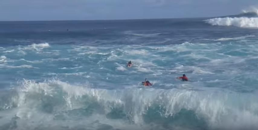 ハワイの大波のポイントJAWSへと向かうサーファー