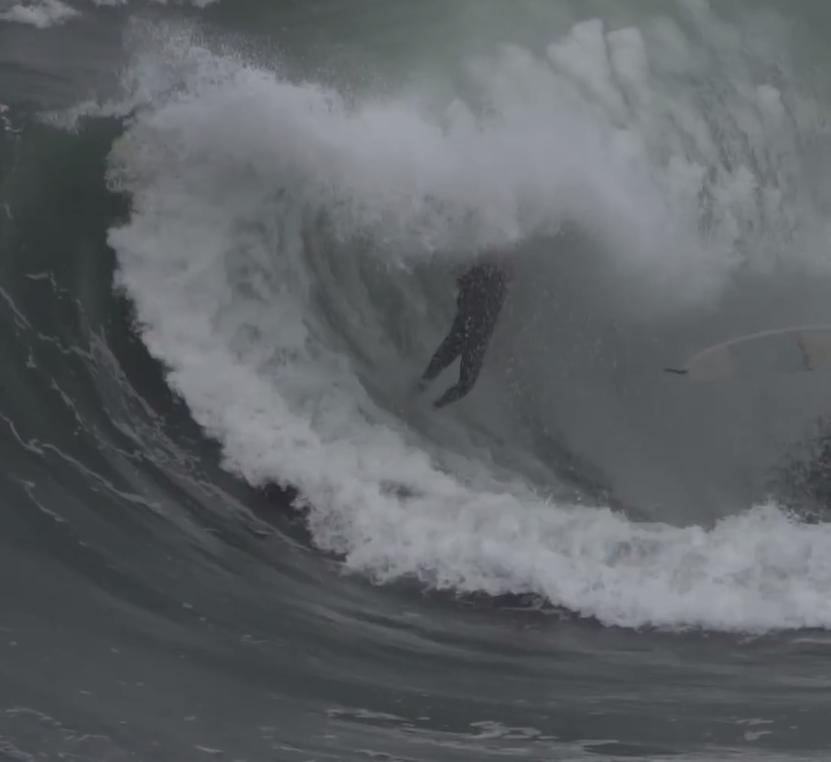 情け容赦ない波の巻き込みを受けるサーファー